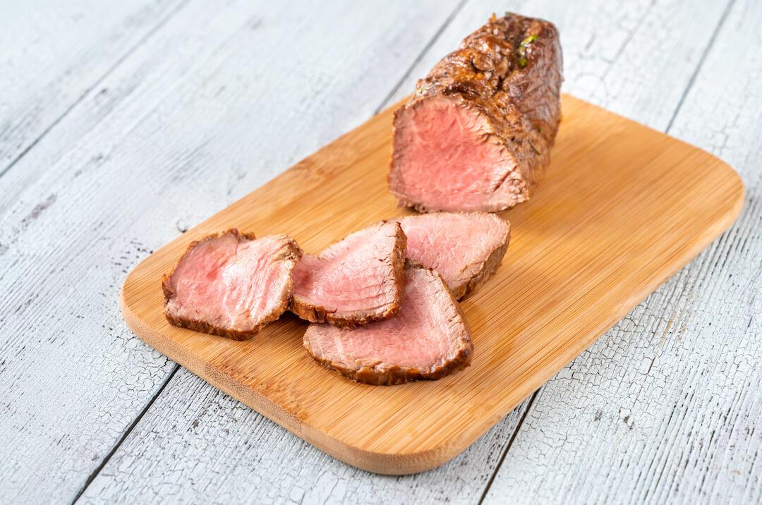 Sliced roast beef on a wooden board